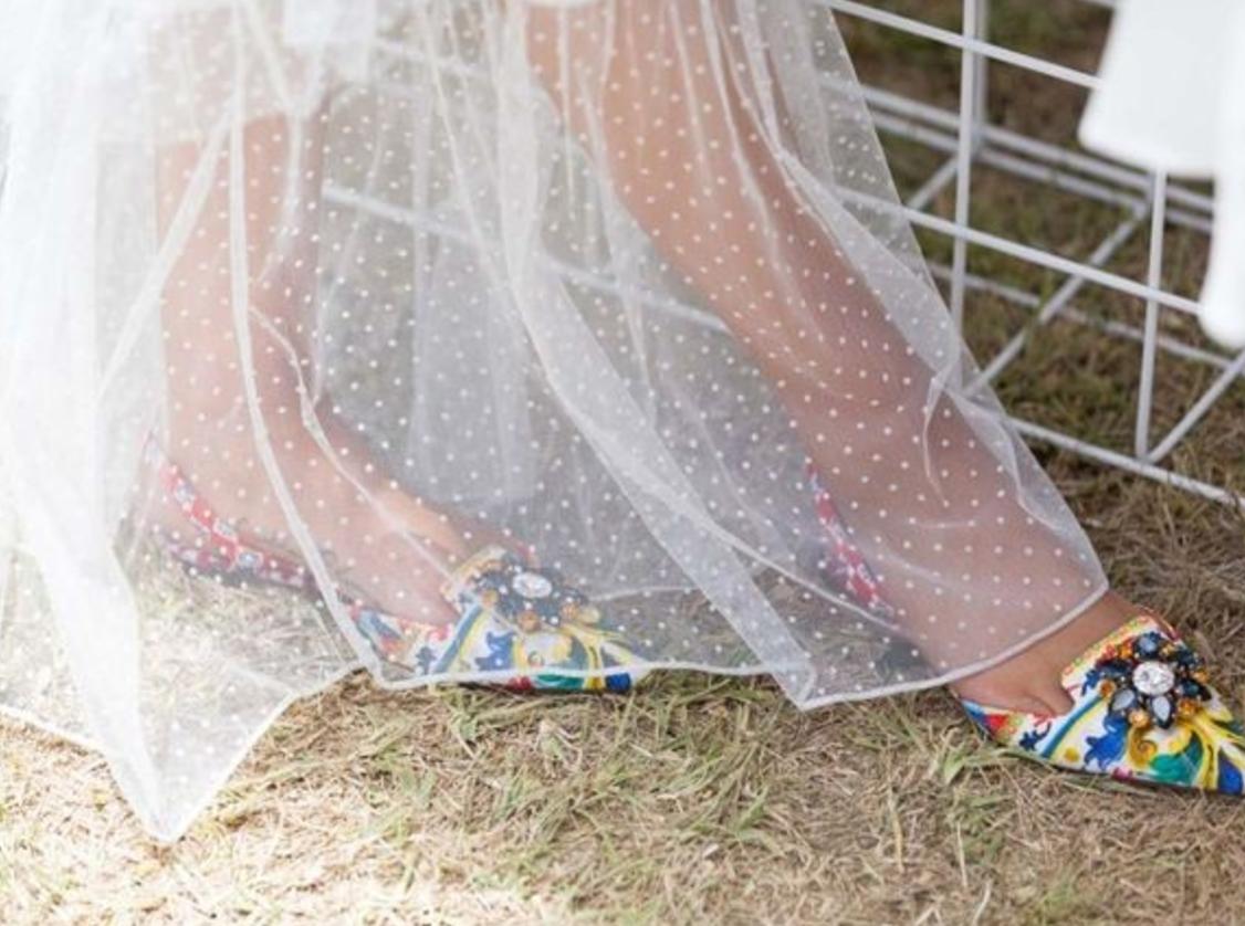 Dolce & Gabbana flats peek through a mesh skirt.