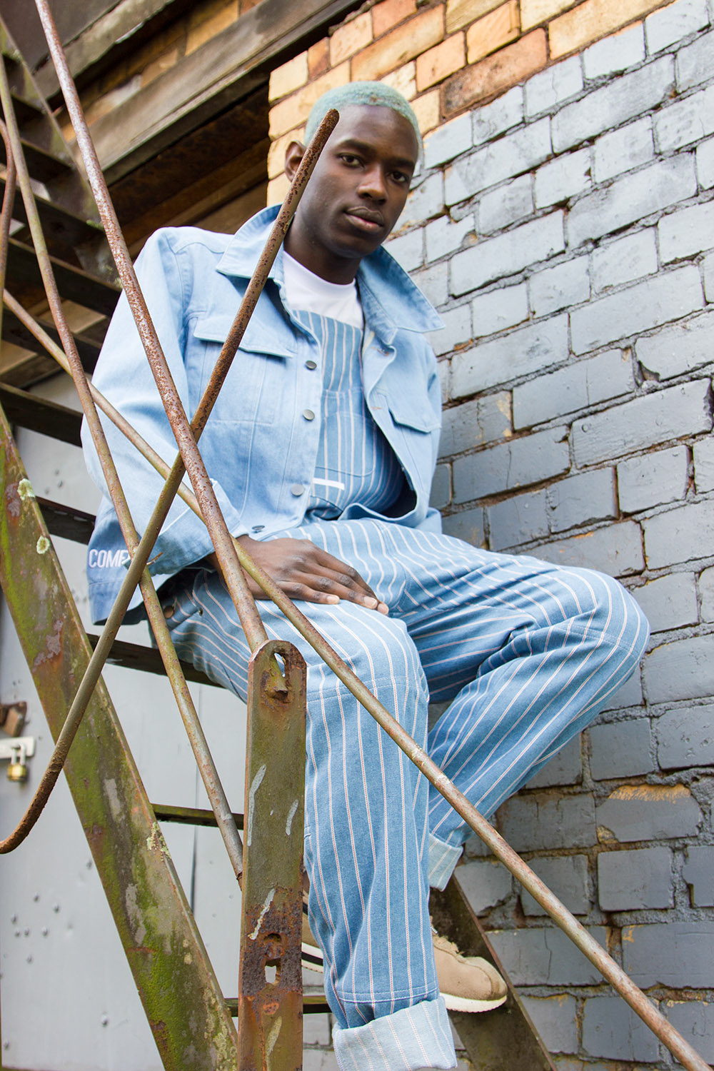 out of comfort menswear worn by masculine-presenting model sitting on steps