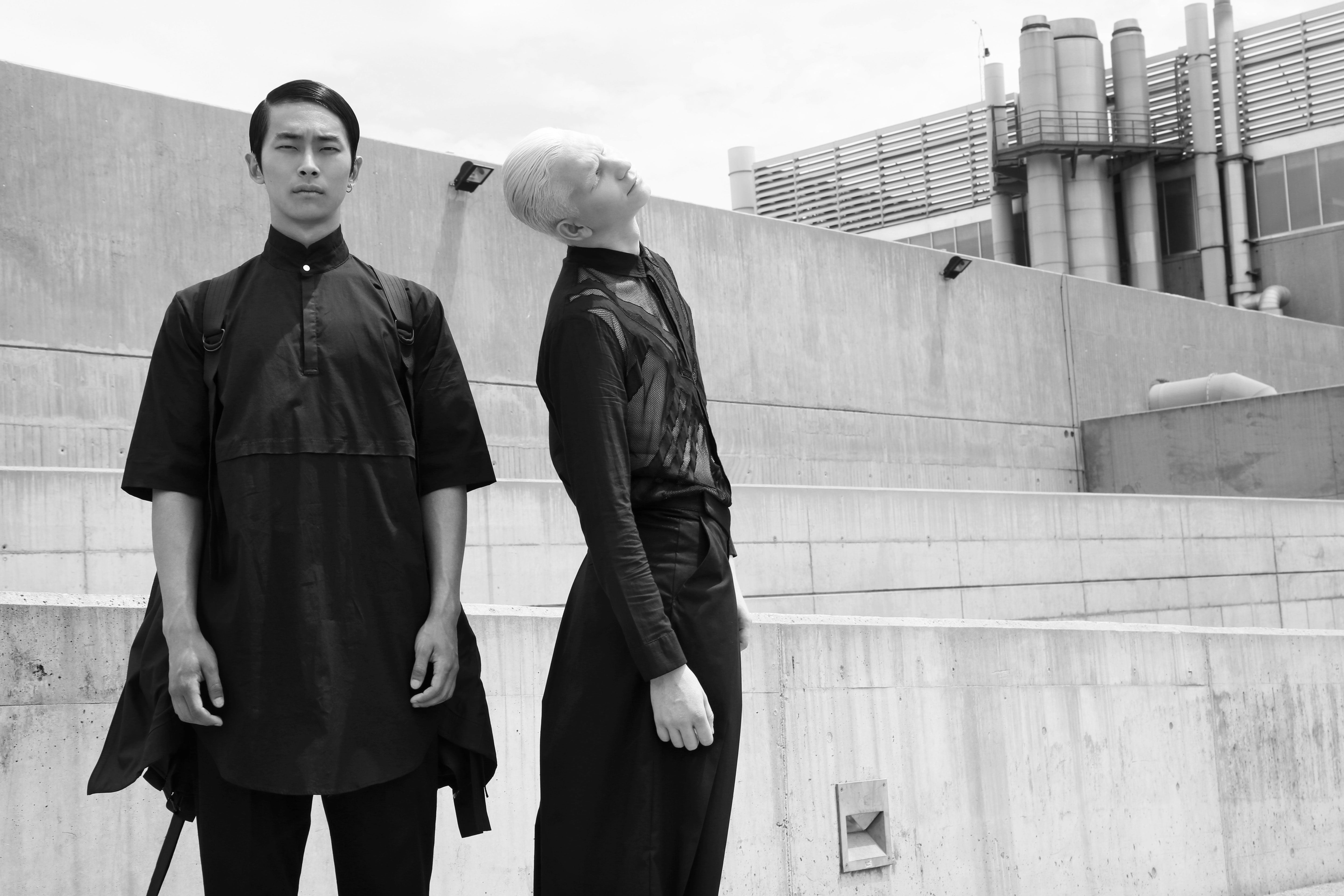 jnorig menswear. two models against a grey background, all dressed in structured black.