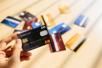 credit cards all over the ground except one, grasped tightly in the fist of a prospective shopper