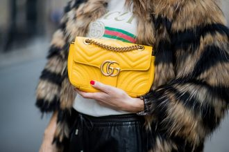 gucci bag held by woman in gucci shirt with fur coat