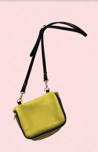 kate of arcadia yellow bag hangs against a pink background
